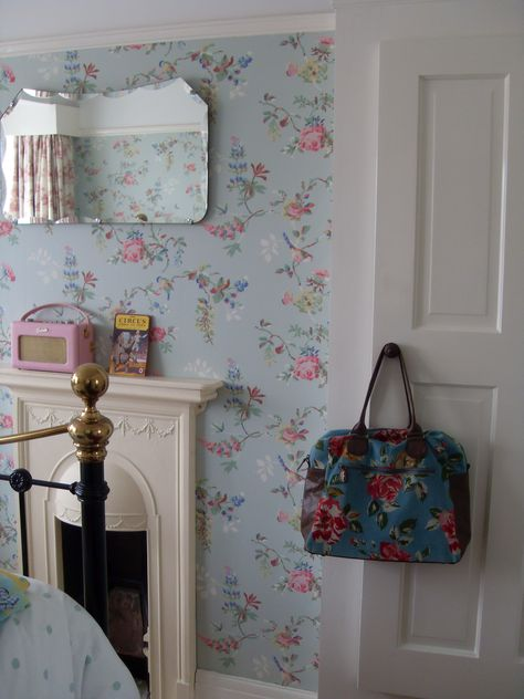 Small bedroom fireplace surrounded by blue floral wallpaper.