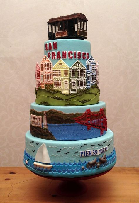 tier cake of San Francisco with different scenes on each tier (SF Bay/Pier Golden Gate Bridge/Alcatraz, pastel Victorian houses, and a Cable Car sculpture on top.