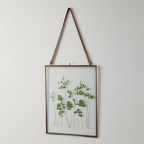 frame of mind. Handmade brass frames with clear glass overlays float fav photos, memories, even dried botanicals.  Natural leather hanging strap delivers accessory appeal.  Even better: brass frames antique over time to a treasured patina. HandmadeBrass frameBrass antique finishWipe clean with soft, dry clothMade in India.