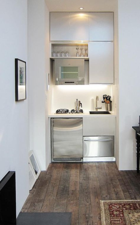 Mesh Architectures' kitchen occupies a nook in a 300-square-foot art dealer's studio. The high-mounted oven includes a space saving feature where the bottom drops down for you to insert the food then retracts back up into the heat. See: Remodelista's Favorite Space Saving Appliances for Small Kitchens. http://www.remodelista.com/posts/5-favorites-Tiny-Kitchen-Roundup