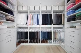 Very symmetrical walk in closet dressing room, white with bleached wood floors