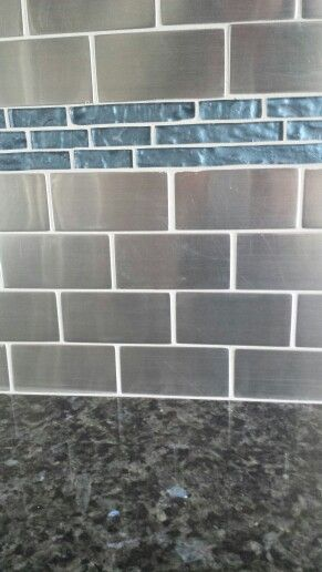 Stainless tile kitchen backsplash with dark blue glass tile