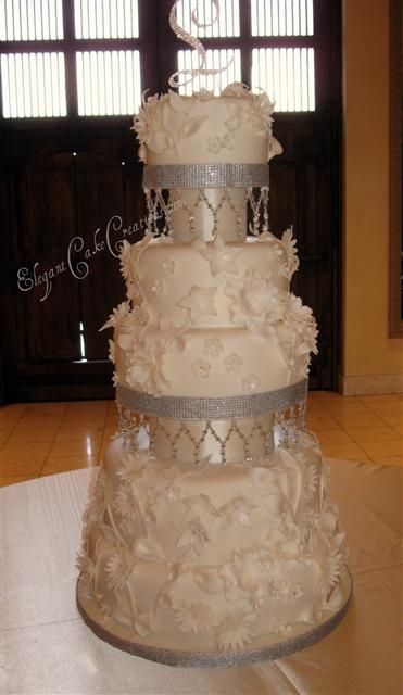All white complimented by glittery bling by Elegant Cake creations : http://www.elegantcakecreations.com/Pages/WeddingCakes.aspx#