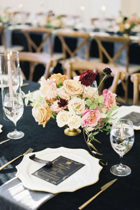 From the editorial Think Ranch Wedding Venues Are Too Rustic? Think Again. The foundation for this design was a black velvet linen, as it felt both chic and elevated while also contributing to the darker mood that the groom loves. Paired with gold and ivory petal chargers to bring in a feminine edge, the final reception look was absolutely breathtaking.  Photography: @sophiekayephotography  #weddingreception #rusticreception #romanticwedding #barnwedding #barnvenue