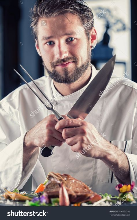 Chef with knife and fork arms crossed. Professional chef in a restaurant or hotel prepares or cut up T-bone steak. Cook for their work on catering