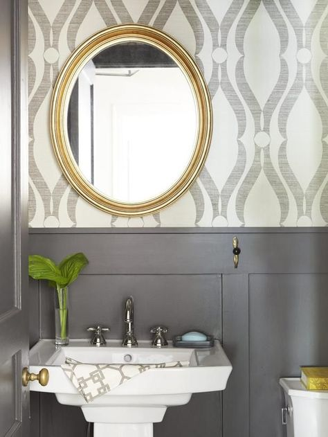Printed grass-cloth wallpaper, gray wainscoting, gold mirror.