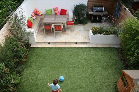 aménagement petit jardin dans l'arrière-cour avec banc en bois, coussins décoratifs et gazon artificiel