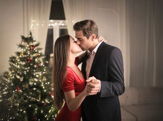 Romantic Couple Kissing While Dancing In Front Of A Christmas Tree