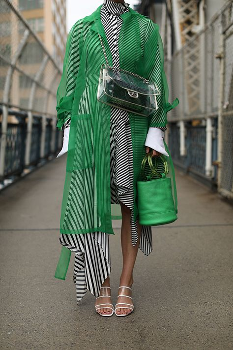 Blair Eadie wearing a green translucent trench and clear mules by Zara // Striped dress by Monse // Green bucket bag by Simon Miller // Clear bag by Chanel // Click through to Atlantic-Pacific for more clear and translucent spring picks