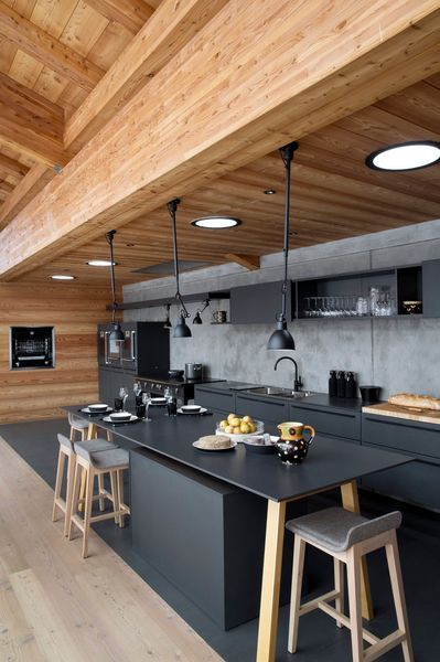 Cuisine tout en longueur en mélaminé noir et son mur en béton banché, avec bois