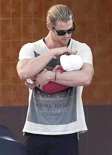 A great idea for a photo with dad...Proud daddy is a sight to behold in shades and muscles holding his newborn in such a gentle caring manner.