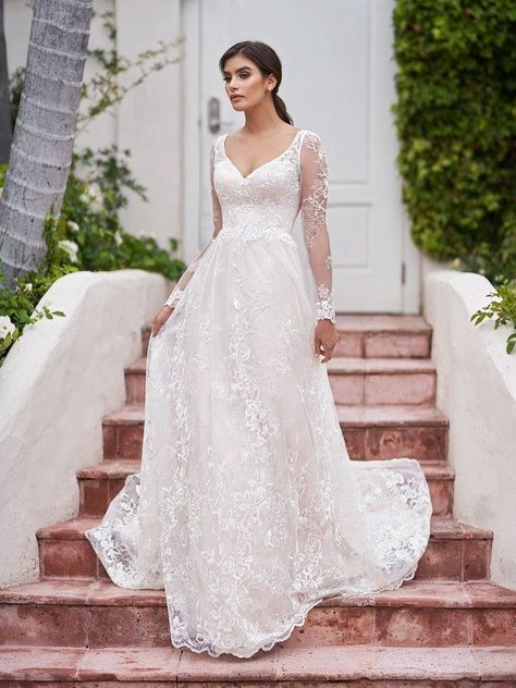 Allure your guests while walking down the aisle in style Surfside from Simply Val Stefani. Long illusion lace sleeves trace along your arms while a sexy v-neckline sits on the fitted bodice. Soft embroidered lace appliques run throughout this A-line silhouette for an organic bohemian style, perfect for the rustic bride. #alineweddingdress #laceweddingdress #rusticbride #longsleeveweddingdress