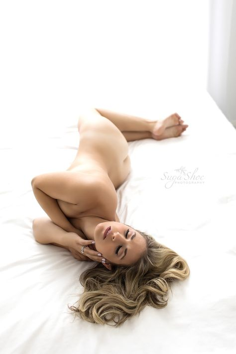 Boudoir pose laying on side on bed naked with hands covering breast and in  hair fb2667104