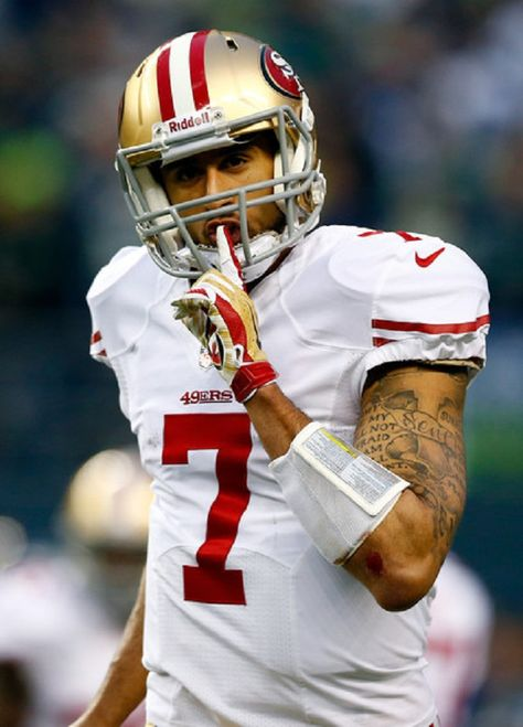 Quarterback Colin Kaepernick #7 of the San Francisco 49ers reacts after teammate running back Anthony Dixon #24 scores a one-yard touchdown against the Seattle Seahawks during the 2014 NFC Championship at CenturyLink Field in Seattle, Washington.