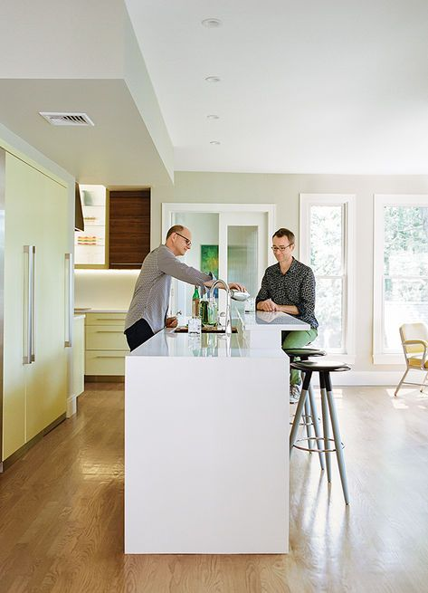 "Dan Pacek and John Roynon prepare cocktails at their 12-foot ""display island"" in the renovated kitchen of their home in New Jersey. Photo by Brian W. Ferry."