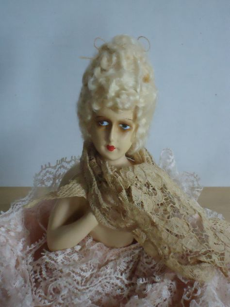 This is a beautifully detailed vintage 1925 German chalkware boudoir/ half doll. Her dark shadowed blue eyes and Clara Bow lips draw you in. With elbows extended and her hands gracefully resting on her chest a lace scarf draped at her neck, she sits surrounded by a long full skirt featuring rows upon rows of vintage pink lace. With her skirt slipped over a wire frame she could easily be transformed into a boudoir lamp for your dressing table. Still retaining her original wig and in incredible...