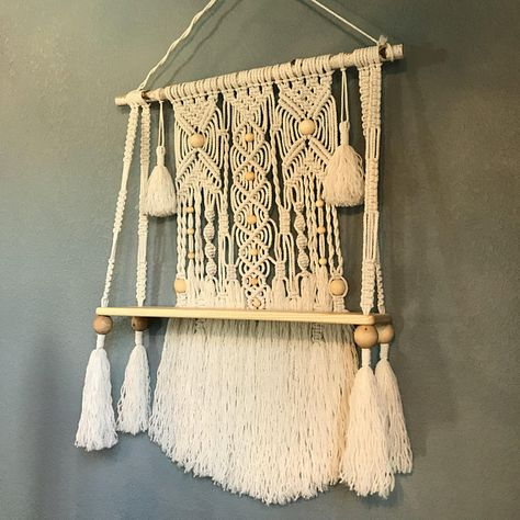 "This is a macrame wall hanging with a natural wood shelf attached. The shelf measures 27""w x 7.5d x 1""thick. The macrame is attached to a birch branch measuring 31"" wide. The macrame design measures 40""long x 27""wide and is made with 100% cotton rope in a lamb's wool color. The"