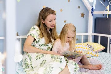 Young Happy Mother And Her Daughter Reading A Book While Sitting