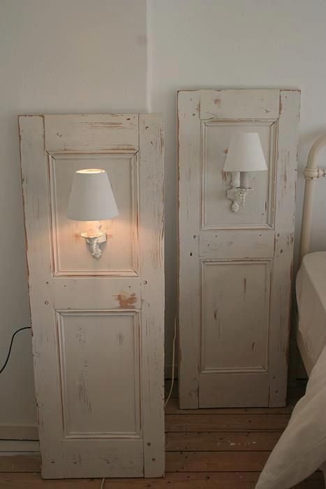 Repurposed cabinet doors to hold sconces.  Great idea for renters or those hesitant to put holes in the walls.