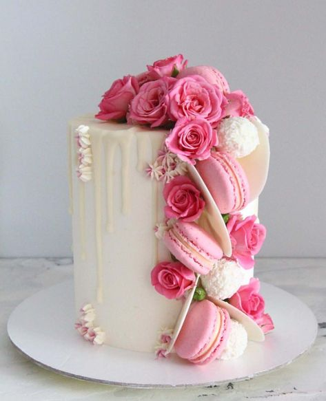 Beautiful white drip cake adorned with pink flowers and macarons