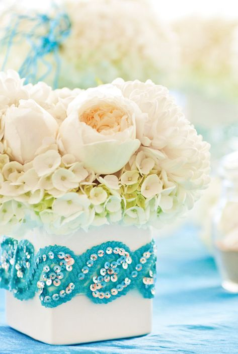 A sequin flower box adds fun to a white floral centerpiece