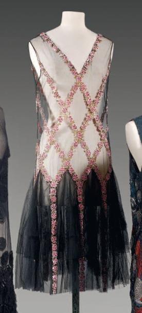 Anonyme, haute couture, circa 1925  Robe en tulle noir brodé de paillettes, de perles roses à motif de fleurettes se rejoignant par un feuillage de paillettes or et formant des losanges tombant sur les quillesà partir des hanches d'une jupe à volant ,décolleté en pointe, sans manches