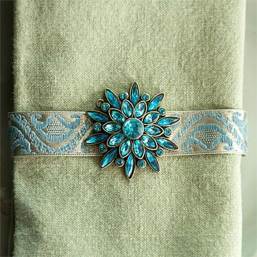 Bejeweled Napkin Ring :: Repurpose old brooches and other jewelry pieces as creative napkin rings. Cut a length of ribbon to fit around a napkin; glue the ends together and let dry. Pin a brooch to the ribbon. Slip the ribbon around a folded napkin and wait for dinner guests to be dazzled.