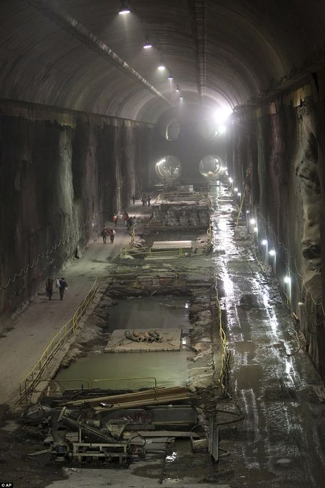 design:Workers walk through a massive eight-story cavern at the East Side Access project beneath midtown Manhattan. The project will bring subway and commuter rail service to the far East and West sides of the city.
