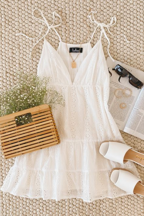 Whether you're scouring the beach for seashells or posted up on a patio, the Lulus Beyond the Boardwalk White Eyelet Lace Tiered Babydoll Dress is a summertime fave! Lightweight woven cotton is pierced with breezy eyelet embroidery as it shapes a deep V-neckline, tying tank straps, and gathered cups. Tiered babydoll silhouette falls to a mini hem. #lovelulus