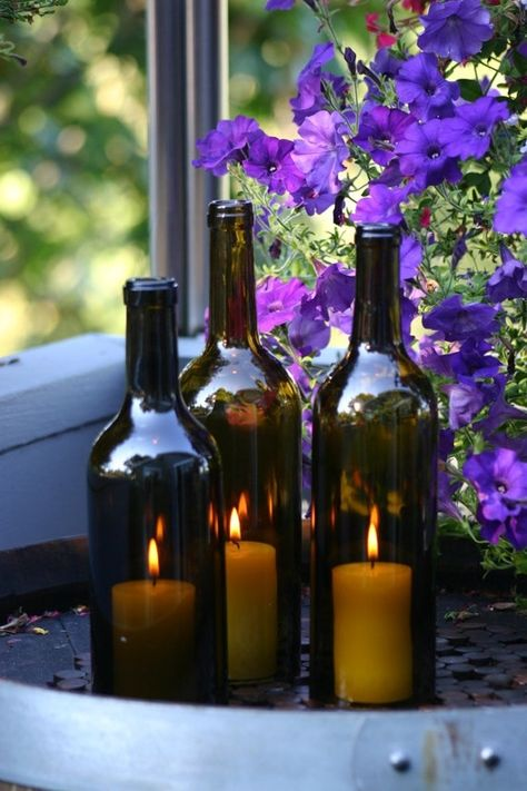 Wine bottles with candles inside by darcy