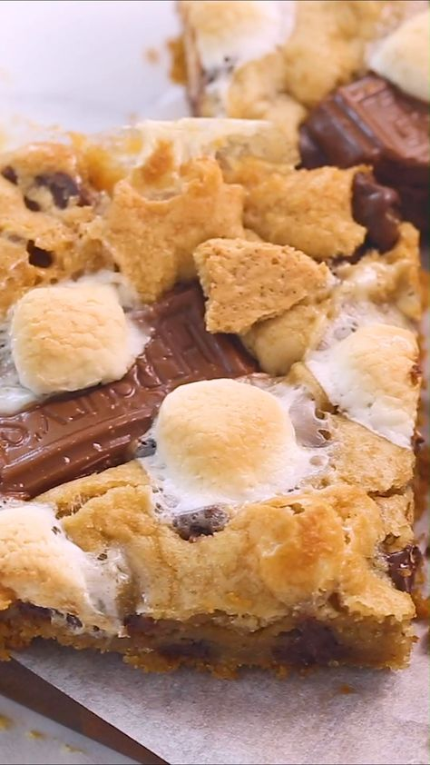 Gooey s'mores bars filled with a graham cracker crust and loaded with chocolate chips, marshmallows and chocolate candy bar pieces. The ultimate cookie bar recipe that is out of this world! #cookiebars #smores #smoresbar #desserts #dessertrecipes #dessertideas #easydesserts #sweets #easyrecipe #recipes #food #foodrecipes #videos #foodvideos #recipevideos #iheartnaptime
