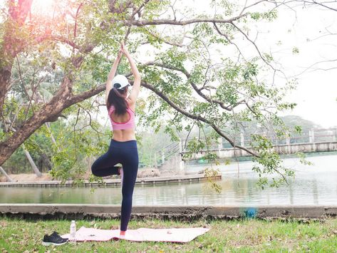 rear view of slim woman in yoga wear doing yoga pose in