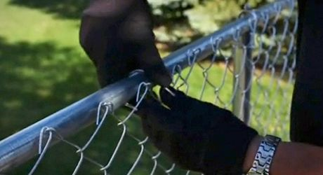 A Person Ties A Chain Link Fence To A Rail Chain Link Fence