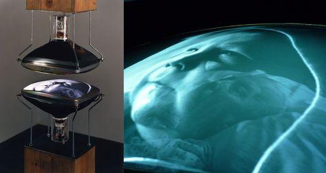 """Bill Viola - """"Heaven and Earth"""" (Video installation, 1992): L'opera espone due video monitor in bianco e nero, posizionati uno di fronte all'altro, separati da pochi centimetri e montati alle estremità di due colonne di legno che si estendono verticalmente dal pavimento e soffitto.  I video riprendono la mamma e il figlio di Bill Viola. Video: https://www.youtube.com/watch?v=csx4kSa9GyE"""