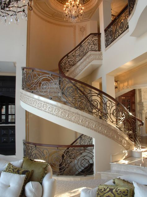 A carved circular staircase in this custom-built, estate-size home features elaborate wrought-iron rails with a swirling design that mimics the lines of the staircase. Above the stairway, a crystal chandelier is suspended from a stained glass dome.