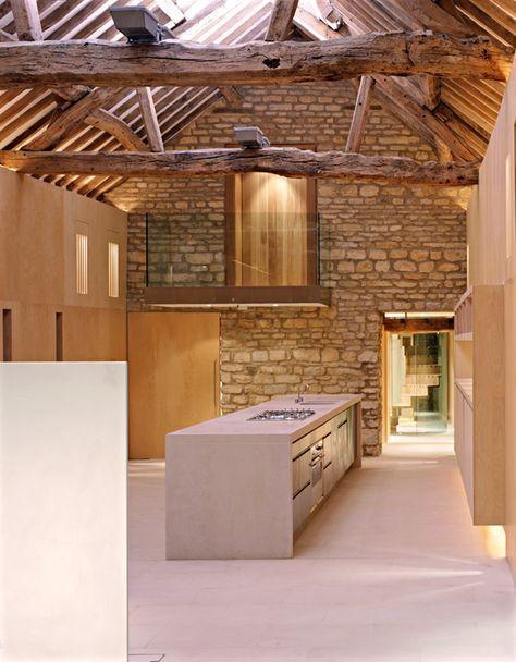 cocina en vivienda rehabilitada, isla central con fregadero y zona de cocción, vigas de madera, pared de piedra, módulos de madera como separación de espacios