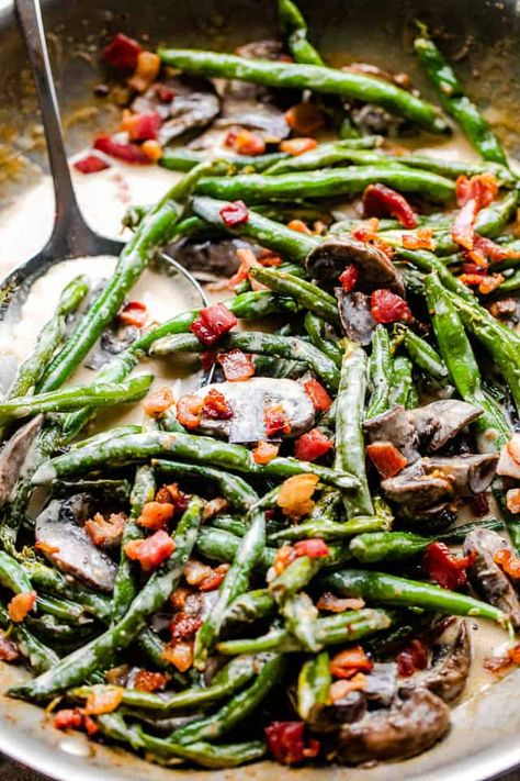 Fresh green beans and mushrooms are sautéed with garlic, sauced up with real cream and aged parmesan, and topped with crispy crumbles of bacon in this easy side dish recipe. #greenbeans #bacon #lowcarbrecipes