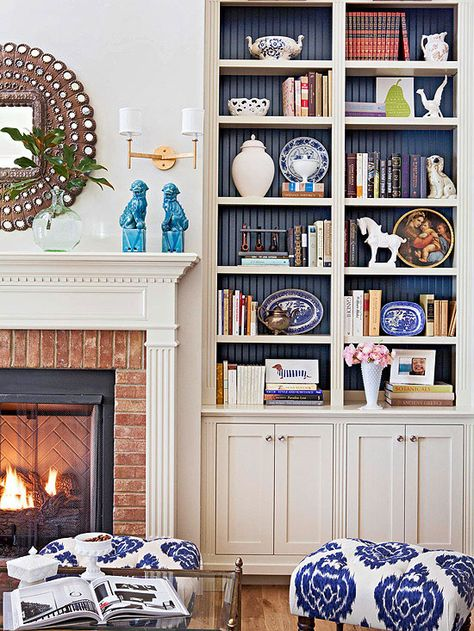 """Built-In Beauties: A pair of tall, narrow bookshelves flank both sides of the fireplace in this spacious living room. The upper portion of the shelves is used to display books and other collectibles, while the lower part is outfitted with a cabinet to stow away games, DVDs, and more. The brick fireplace surround adds a dash of rough, stony texture."""