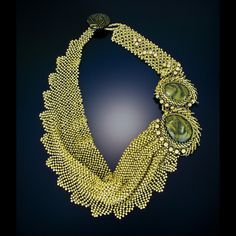 Scarf designed necklace of seed beads with handmade cabochon as accents.