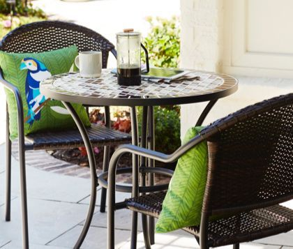A Patio Bistro Set With A Table Two Chairs And Green Pillows