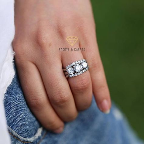 This fine three stone round brilliant cut solitaire engagement ring and bridal set features 2.5 carats of round brilliant cut lab created diamond simulants hand set on solid 14 karat white gold. This engagement ring set comes with 2 matching wedding bands also made in 14k white gold.