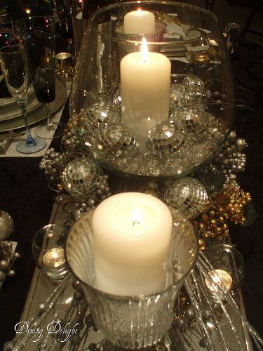 White glass filler in a large fish bowl with silver/white ornaments, mixed with mercury glass/New Year's Eve Tablescape