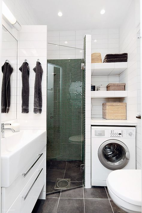 Corner shower with vanity on one side & washer/dryer/linen closet on other side. Toilet across from toilet.