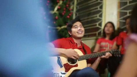 This is the handsome Paulo Avelino playing an acoustic guitar and ...