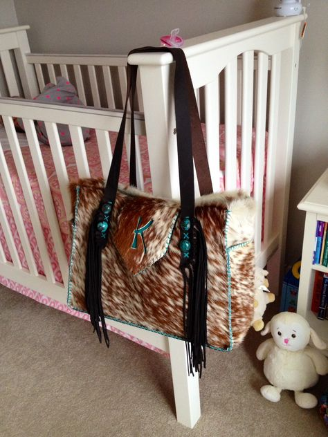 """The Buckaroo Diaper Tote. Customized with suede lined side pockets to hold extra bottles, a """"K"""" brand and turquoise stones. From gowestdesigns.us"""