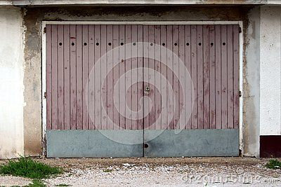 Garage Doors Made Of Dilapidated Wooden Boards With Metal Plate Rain Protection Mounted On Cracked Old Wall With Gravel Mixed Old Wall Dilapidated Wooden Board