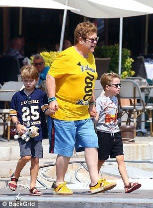 Colourful! Elton couldn't be missed his bright ensemble as his children opted for fun summ...