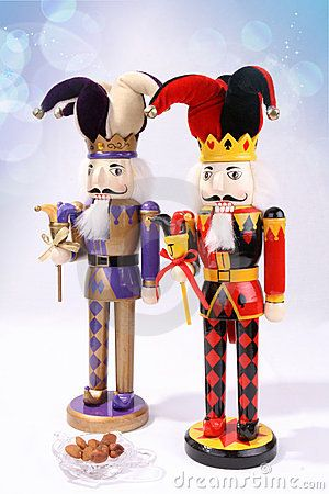 nutcrackers | Two wooden nutcrackers with a plate of nuts on artistic background