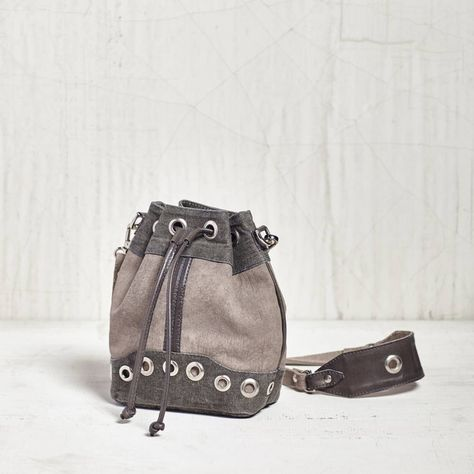 """The Bucket List Canvas Mini Crossbody gives you a lot of storage space in a mini size that will never weigh you down. With all the wonderful embellishments that this bag has to offer, who can resist! Featured in contrasting gray canvas with leather and grommet accents and a 23"""" strap. This chic litle bag is ready for some fun around town! Measures7.25"""" W x 8.5"""" H x 4.25"""" D Waste not, is the concept behind these awesome bags from Mona B. Why make new materials when there ..."""