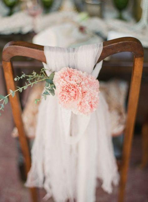 Preciosa decoración de las sillas con tela de gasa y claveles rosados